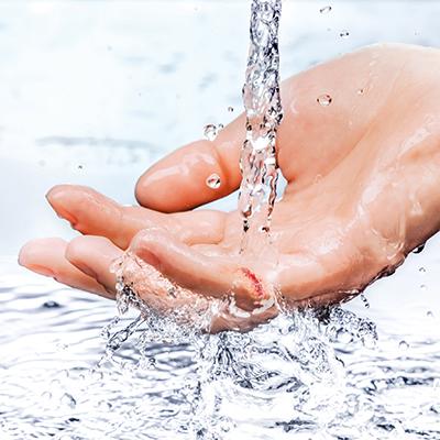 Wunde an Finger wird mit Wasser gereinigt.